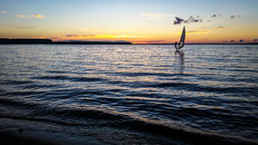 Windsurfer sailing in the lake at sunset. Stock Image