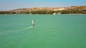 Windsurfer sails on ocean in coast direction stock video