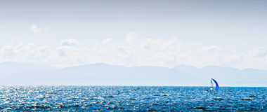 Windsurfer in the sea bay at the summer. Wind surfer in the sea bay against horizon, mountains and deep blue sky Stock Photography