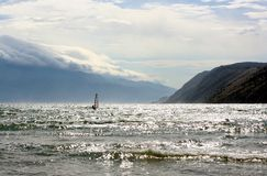 Windsurfer on a sea, mountains and clouds Stock Photos