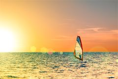Windsurfer in the sea with a scenic sunset sky. Toned, lens sun flare. Active sport vacation concept.  Stock Image