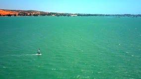 Windsurfer segelt in offenen Ozean gegen entfernte Küste stock video footage