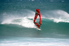 Windsurfer Shooting a Good Wave. A windsurfer with a red sail coming down the face of a blue wave in Hawaiian waters Royalty Free Stock Photo