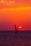Windsurfer silhouette against sun Royalty Free Stock Image
