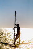 Windsurfer silhouette against sun Royalty Free Stock Images