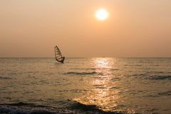 Windsurfer silhouette in front of sunset background. Windsurfer silhouette in front of a sunset background on the horizon Royalty Free Stock Photo