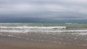 Windsurfer solo en la línea de mar y ondas debajo de las nubes oscuras