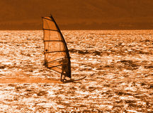 Windsurfer at Sunset. A teenage windsurfer catches a last ride before sundown on a southern beach in Maui, Hawaii Stock Photo