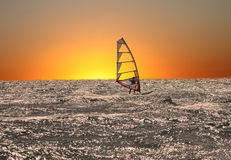 Windsurfer at sunset. Windsurfing on the ocean at sunset Stock Images