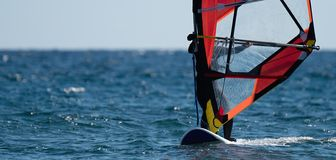 Windsurfer surfing the wind on waves in ocean. Recreational sporting activity royalty free stock photos