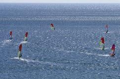 7 windsurfers едут на поверхности ослеплять красивого Средиземного моря Стоковая Фотография