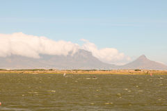Windsurfers auf Rietvlei im Tabellen-Bucht-Naturreservat mit Tafelberg im Hintergrund, Cape Town, Südafrika Stockfotografie