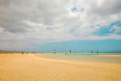Windsurfers on the beach Playa de Sotavento on the Canary Island. Windsurfers on the beach Playa de Sotavento in a cloudy day in summer on the Canary Island Stock Images