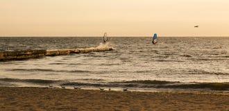 Windsurfers en el mar durante la salida del sol Imagenes de archivo