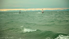 Windsurfers enjoy windy weather. Windsurfers taking the advantage of winds and surf the waves stock video