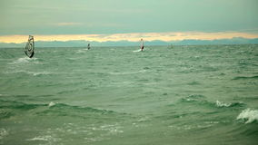 Windsurfers out in the open sea. Windsurfers taking the advantage of winds and surf the waves stock video footage