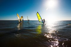 Windsurfers silhouettieren gegen einen Sonnenunterganghintergrund, aktiver Lebensstil Lizenzfreie Stockfotos