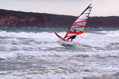 Windsurfing. Windsurfer jumping waves on a stormy day Royalty Free Stock Images