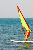 Windsurfing. Windsurfer, blue sea and yellow sail stock image