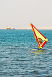 Windsurfing. Windsurfer, blue sea and yellow sail on sunset Royalty Free Stock Images