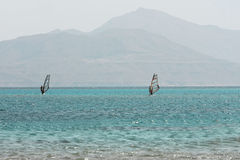 Windsurfing. Two windsurfers, blue sea and mount background stock photo