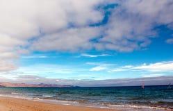 Windsurfing along long empty beach. Windsurfing along empty sandy beach, Fuerteventura island Stock Photo
