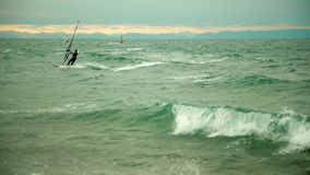 Windsurfing in the bad weather. Windsurfers taking the advantage of winds and surf the waves stock footage