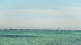 Windsurfing in beautiful clear water in Dahab Egypt. Exploring the blue water with mountains in the background and
