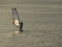 Windsurfing bij zonsondergang met kalme overzees stock foto's