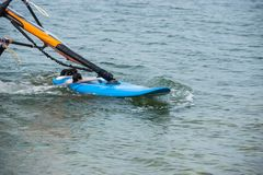 Windsurfing details. A windsurfer rides on the sea. Windsurfing details, blue Board. A windsurfer rides on the sea royalty free stock images