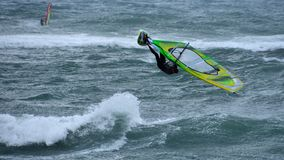 Windsurfing high jump in storm stock image