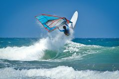 Windsurfing jumps out of the water. Very high above the wave stock images