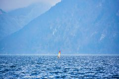 Windsurfing on lake landscape and foggy mountains at background. Man Windsurfer on the Board with a sail floating on the lake.  royalty free stock photos