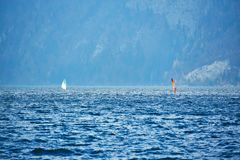 Windsurfing on lake landscape and foggy mountains at background. Man Windsurfer on the Board with a sail floating on the lake.  stock photo