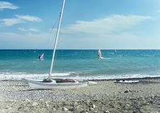 Windsurfing in the Ligurian Sea. And lonely yacht on the beach Royalty Free Stock Photos