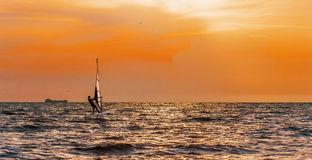 Windsurfing on orange sunset's background. At sea Stock Photos