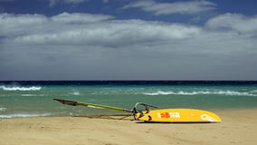 Windsurfing on Risco del Paso beach, Fuerteventura, Canary islands. Windsurfing board left on Risco del Paso beach, Fuerteventura island, Spain. Favorable windy Royalty Free Stock Photo