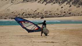 Windsurfing on Risco del Paso beach, Fuerteventura, Canary islands. Girl carrying her windsurfing board on Risco del Paso beach, Fuerteventura island, Spain Stock Photos