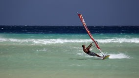 Windsurfing on Risco del Paso beach, Fuerteventura, Canary islands. Man enjoying his windsurfing ride on Risco del Paso beach, Fuerteventura island, Spain. Windy Stock Photo