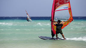 Windsurfing on Risco del Paso beach, Fuerteventura, Canary islands. Men enjoying their windsurfing ride on Risco del Paso beach, Fuerteventura island, Spain Stock Images