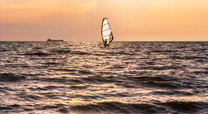 Windsurfing in the sea before the storm. Windsurfing in the sea at sunset on the stormy clouds Royalty Free Stock Photos