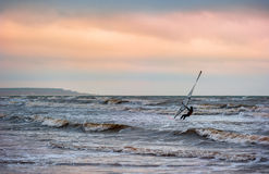 Windsurfing at sunset. Man on windsurfing in the distance. Evening sky, sea after a gale stock image