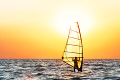 Windsurfing at sunset. Sea windsurfing on a background of orange sunset Stock Photography