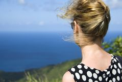 Windswept. A blonde woman looking out to sea from the top of a hill on a windy day royalty free stock photos