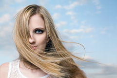 Windswept freedom. Moody portrait of a beautiful young blond woman with flowing windswept hair royalty free stock photo