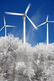 Windtausendstel-Leistunggeneratoren gegen Winterwald Stockfotos