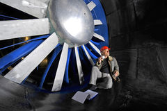 Windtunnel engineer. An engineer, checking up on the mechanical structure inside a windtunnel Stock Image