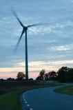 Windturbine bij het winden van weg in een landelijk landschap Stock Afbeelding