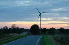 Windturbine door een windende weg bij recente avond Royalty-vrije Stock Foto