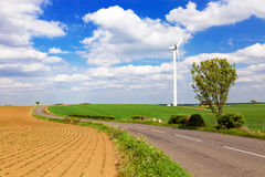 Windturbine in english countryside. Windturbine farm and winding road Stock Photo
